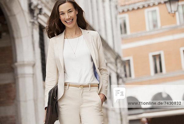 Porträt einer lächelnden Geschäftsfrau beim Gehen