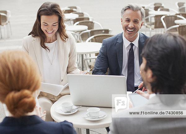 Lachende Geschäftsleute treffen sich im Straßencafé