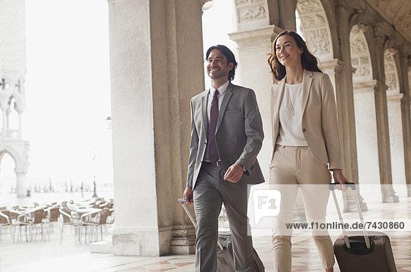 Lächelnder Geschäftsmann und Geschäftsfrau  die Koffer auf dem Flur ziehen