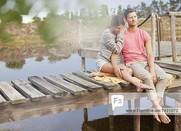 Ein ruhiges Paar  das auf einem Dock über dem See sitzt.