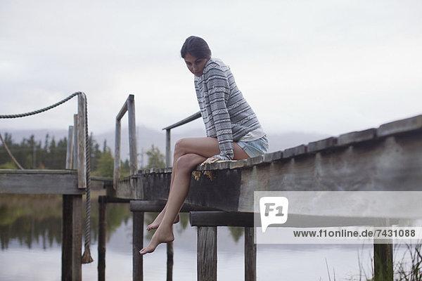 Gelassene Frau am Rande des Docks über dem See sitzend