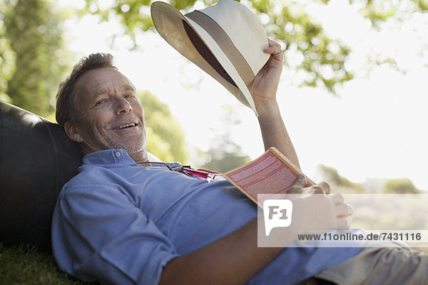 Portrait of smiling man laying on grass with book and hat