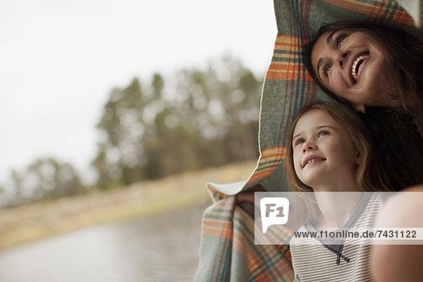 Lächelnde Mutter und Tochter unter der Decke am Seeufer Lächelnde Mutter und Tochter unter der Decke am Seeufer