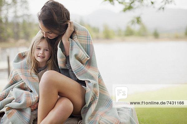 Porträt der lächelnden Tochter in Decke gehüllt mit Mutter am Seeufer