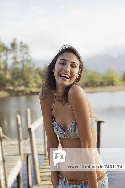 Porträt der begeisterten Frau im Bikini am Seeufer