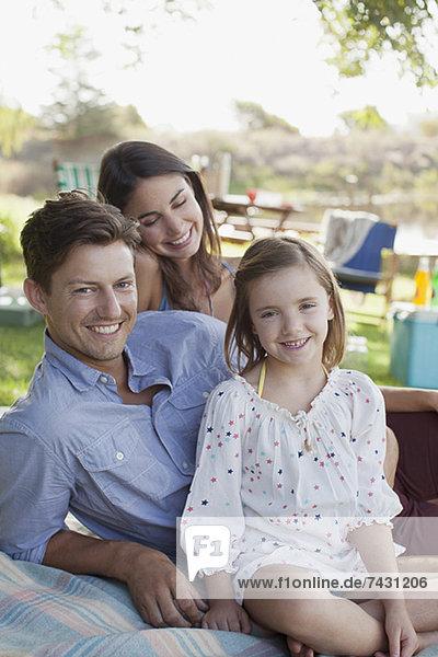 Porträt eines lächelnden Familienpicknicks am Seeufer