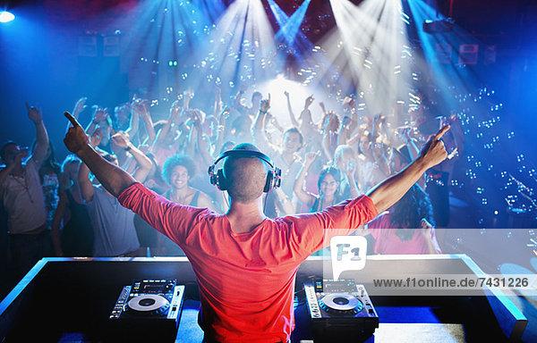 DJ mit ausgestreckten Armen mit Blick auf die Tanzfläche