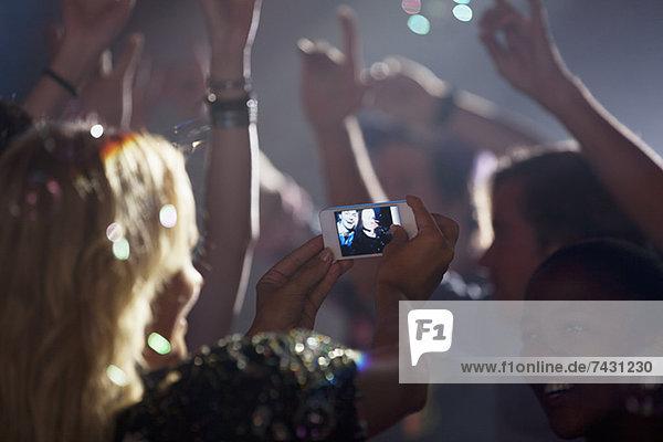 Frau mit Fotohandy beim Fotografieren von Freunden auf der Tanzfläche des Nachtclubs