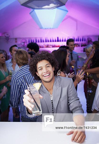 Porträt eines lächelnden Mannes mit Cocktail in der Bar des Nachtclubs