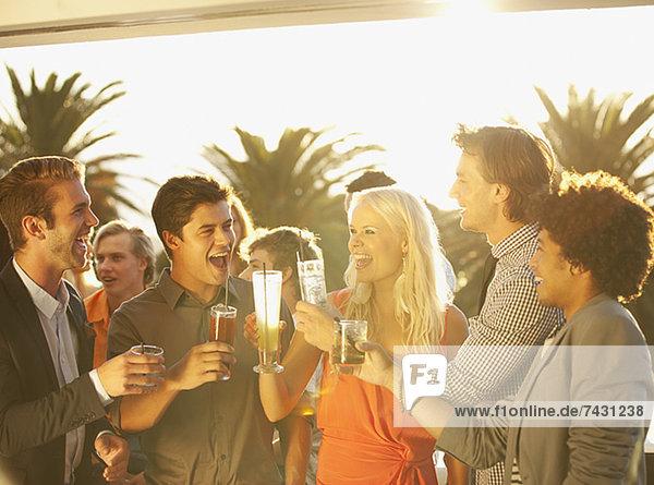 Freunde toasten Cocktails auf dem sonnigen Balkon