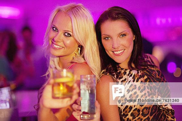 Porträt von lächelnden Frauen  die im Nachtclub auf Cocktails anstoßen.