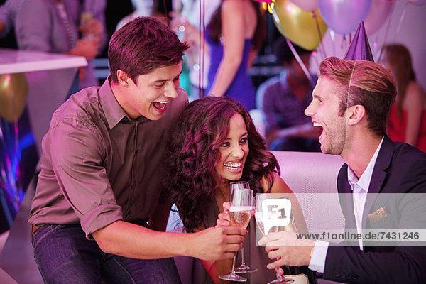 Enthusiastische Freunde toasten Champagnerflöten im Nachtclub