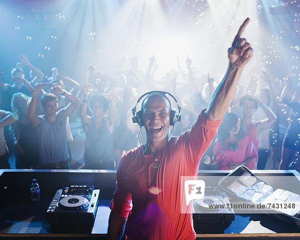 Porträt eines begeisterten DJs mit erhobenem Arm und Menschen auf der Tanzfläche im Hintergrund