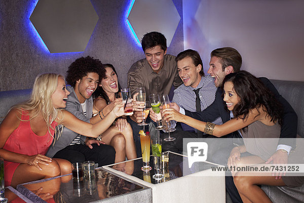 Freunde toasten Cocktails im Nachtclub