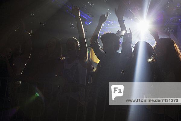 Spotlight über der Silhouette des jubelnden Publikums beim Konzert