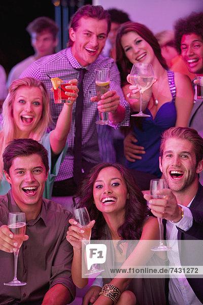 Porträt von lächelnden Freunden  die Cocktails im Nachtclub trinken