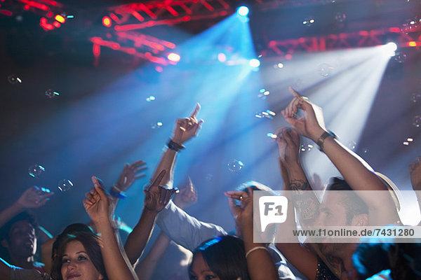 Begeisterte Menge mit erhobenen Armen auf der Tanzfläche des Nachtclubs