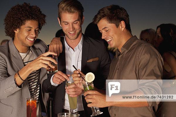 Lächelnde Männer toasten Cocktails im Nachtclub