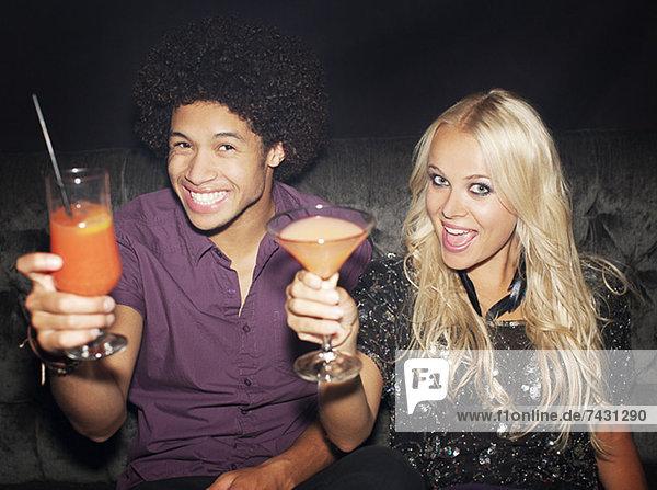 Porträt eines begeisterten Paares  das Cocktails im Nachtclub trinkt.