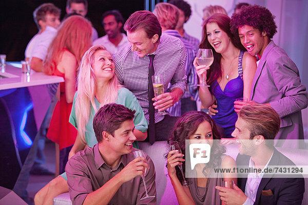 Lächelnde Freunde trinken Champagner im Nachtclub