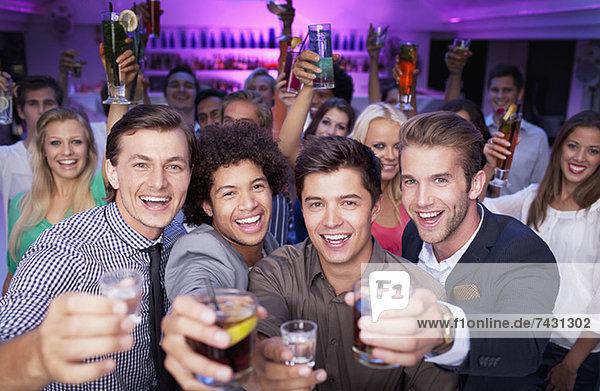 Porträt eines begeisterten Publikums  das Cocktails im Nachtclub trinkt.