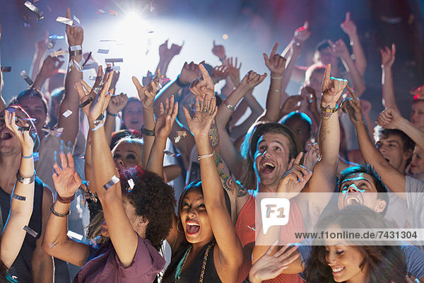 Enthusiastic crowd cheering at concert