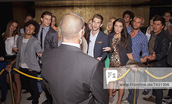 Menschenmenge gestikuliert zum Türsteher hinter dem Seil vor dem Nachtclub