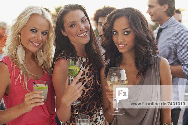 Porträt von lächelnden Frauen beim Trinken von Cocktails