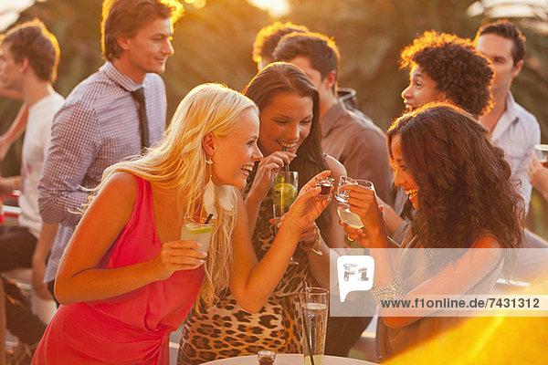 Lächelnde Frauen trinken Cocktails auf dem sonnigen Balkon