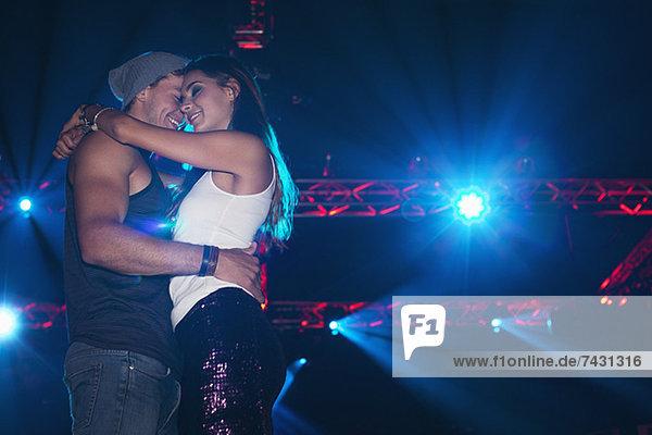 Lächelndes Paar  das sich unter Scheinwerfern im Nachtclub umarmt.