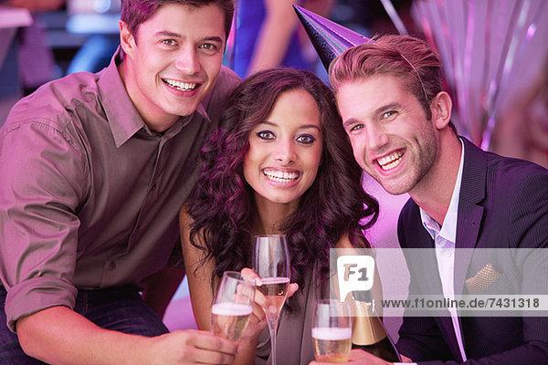 Porträt von lächelnden Freunden beim Champagnertrinken im Nachtclub