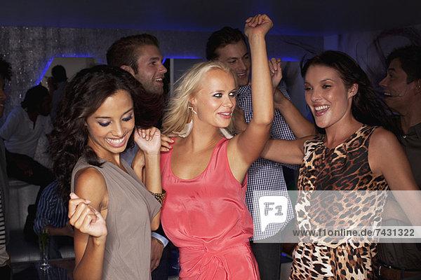Lächelnde Frauen tanzen im Nachtclub