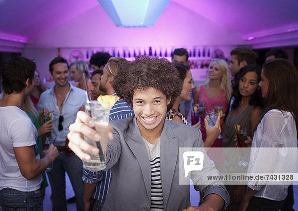 Porträt eines lächelnden Mannes mit Cocktail an der Bar im Nachtclub