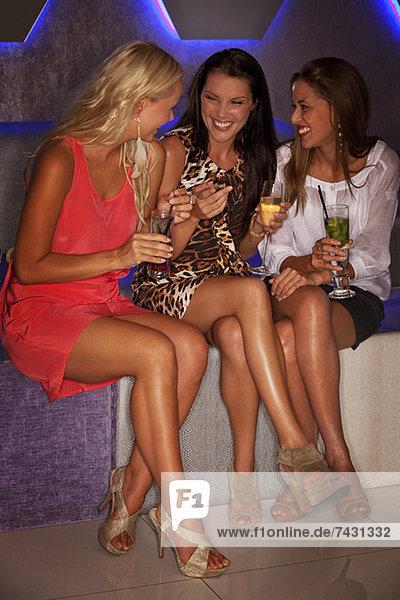 Lächelnde Frauen trinken Cocktails im Nachtclub
