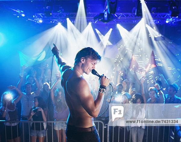 Nackte Sängerin auf der Bühne mit Publikum im Hintergrund
