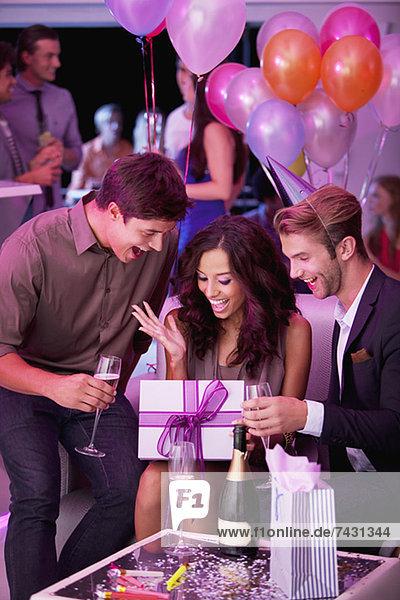 Lächelnde Freunde trinken Champagner und feiern Geburtstag im Nachtclub