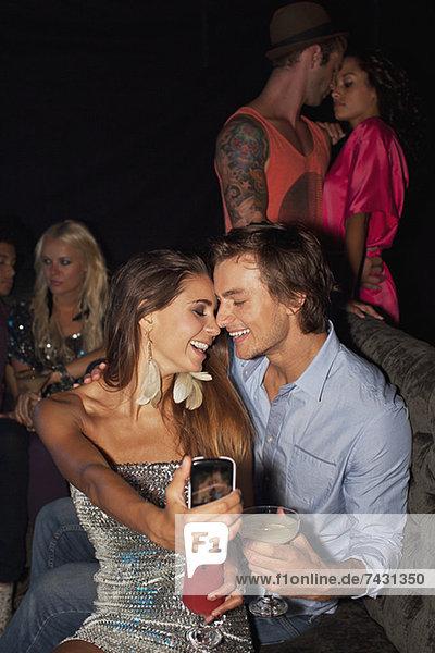 Lächelndes Paar trinkt Cocktails und nimmt Selbstporträt mit Fotohandy im Nachtclub.