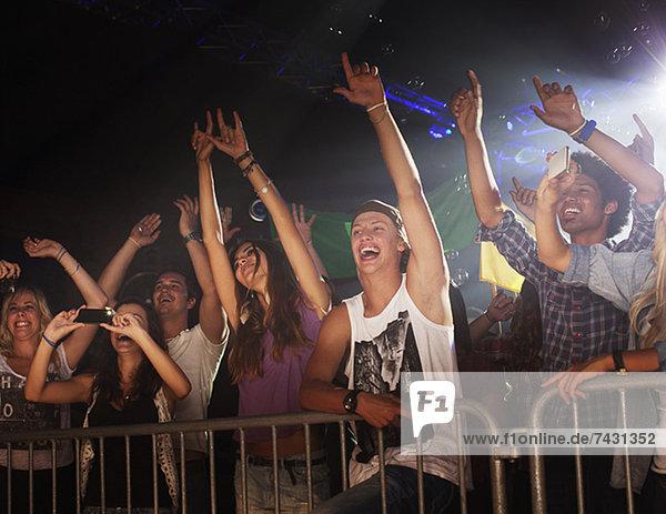 Begeistertes Publikum mit erhobenen Armen hinter dem Geländer beim Konzert