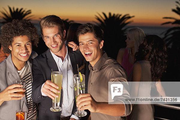 Porträt von lächelnden Männern auf dem Balkon bei Sonnenuntergang