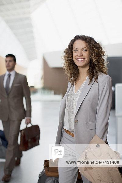 Porträt einer lächelnden Geschäftsfrau mit Koffer am Flughafen
