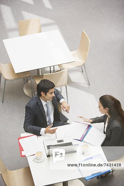 Geschäftsmann und Geschäftsfrau besprechen Papierkram im Café