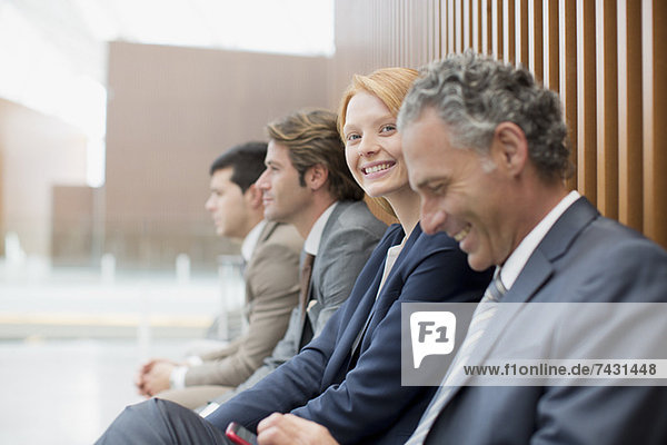 Porträt einer lächelnden Geschäftsfrau  die mit Geschäftsleuten sitzt.