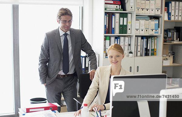 Geschäftsmann und Geschäftsfrau mit Computer am Schreibtisch im Büro