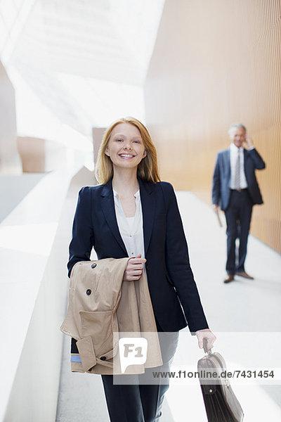 Porträt der lächelnden Geschäftsfrau mit Mantel und Aktentasche