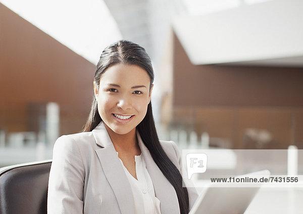 Porträt einer lächelnden Geschäftsfrau mit digitalem Tablett im Büro