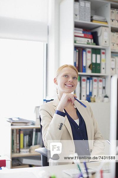 Lächelnde Frau  die im Büro aufschaut