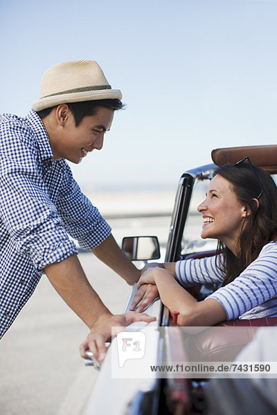 Smiling couple talking in convertible