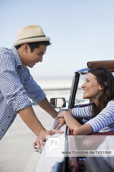 Lächelndes Paar im Cabriolet