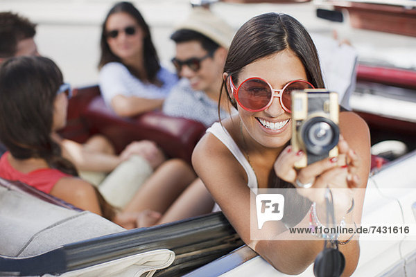 Woman taking picture from convertible