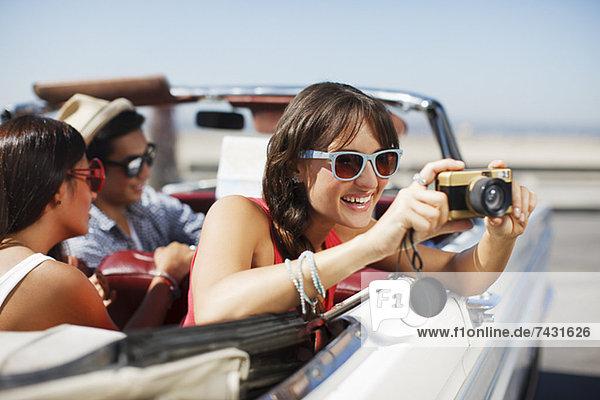 Lächelnde Frau fotografiert vom Cabriolet aus